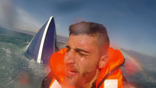 Мигрант, опознанный как 20-летний Пелен Хуссейн из Сирии, с опрокинутой лодкой на заднем плане, был спасен членом воздушного командования береговой охраны Турции в Эгейском море у вод залива Эдремит, Турция, 8 февраля 2016 года. На этом раздаточном материале, предоставленном командованием береговой охраны Турции