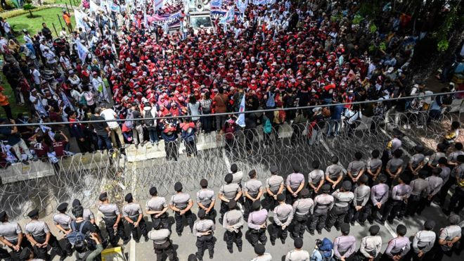 Indonesian activists and workers are blocked by police as they take part in a protest to mark May Day