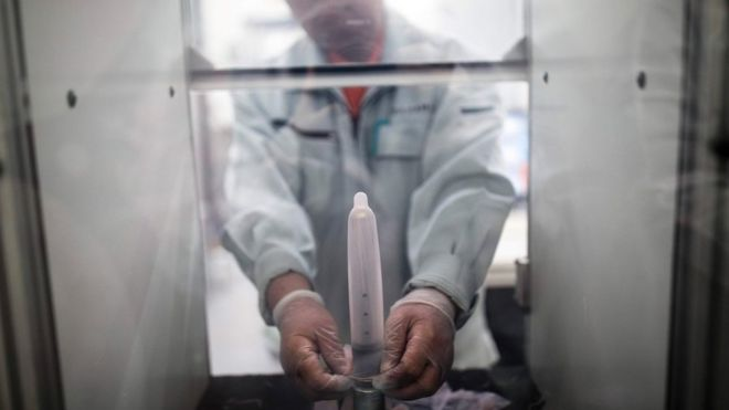 Un empleado del fabricante japonés de condones Sagami Rubber Industries pone un condón en una máquina para probar su resistencia llenándolo de aire.