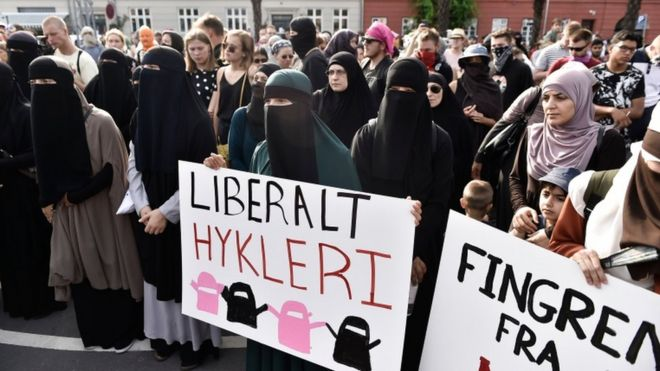 Women in veils protesting with signs