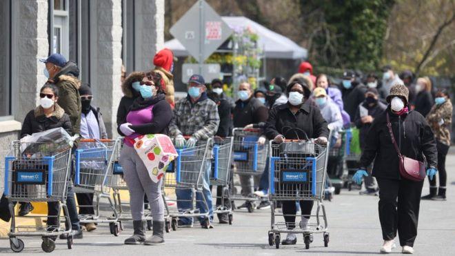Fila de personas ante un supermercado.