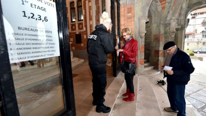 Security personnel help voters in Le Touquet, northern France