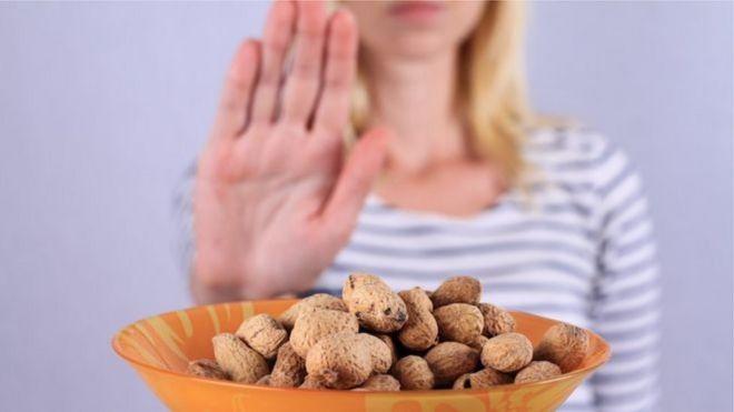 Mulher faz sinal de pare em frente a prato com amendoins