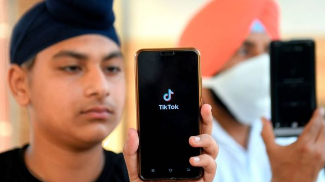 Indian boy with TikTok app opened on phone.