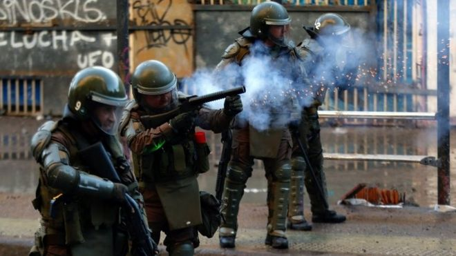 Carabineros fire tear gas on protesters during demonstrations at Plaza Baquedano, in Santiago, Chile, 15 November 2019.