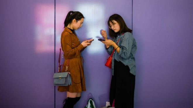 Dos mujeres usando sus celulares en China