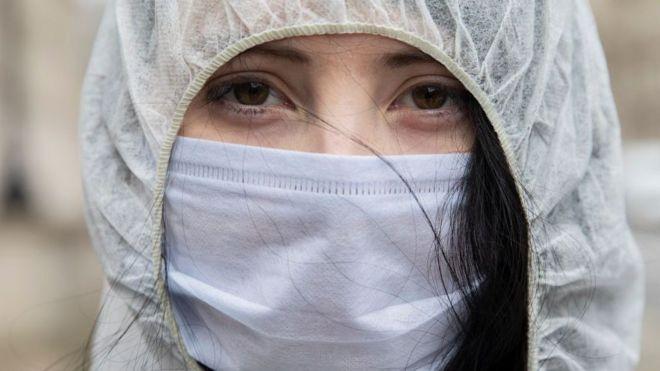 Una mujer joven vistiendo equipo de protección personal y mascarilla.