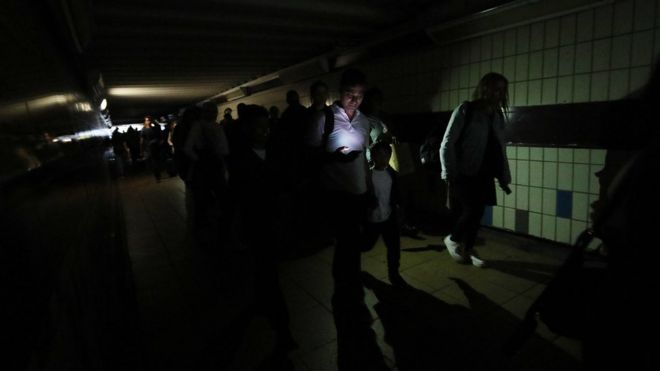 People walking in complete darkness at Clapham Junction station in London during a power cut,