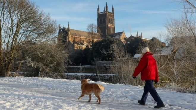 A dog walker on the banks of the River Severn in Worcester