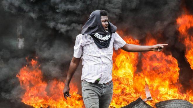 Hombre camina frente a fuego durante unas protestas en Haití