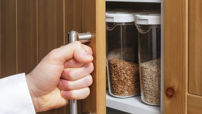 Opening a kitchen cupboard containing storage jars