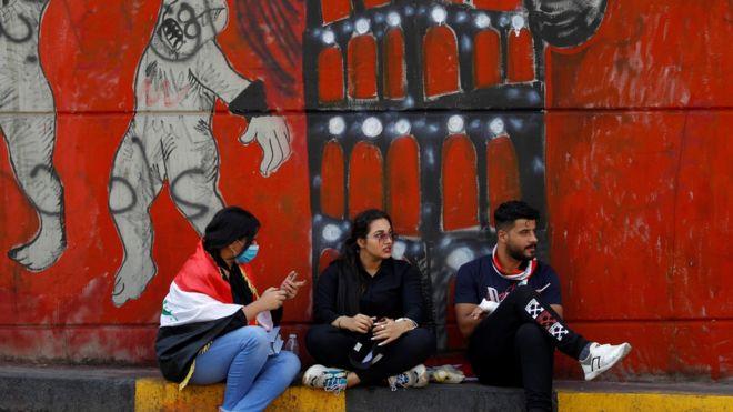 شباب يجلسون أمام جدارية في بغداد