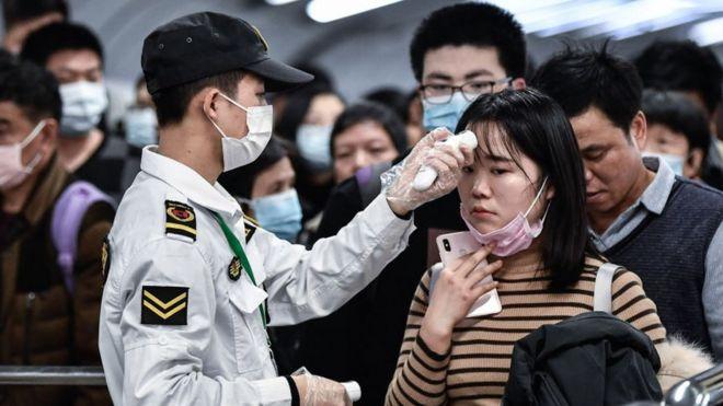 Un agente de seguridad tomando la temperatura a una mujer en China.