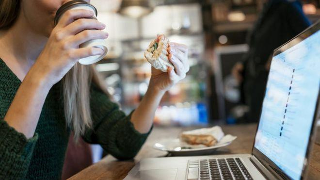 Mulher come sanduíche em frente ao computador