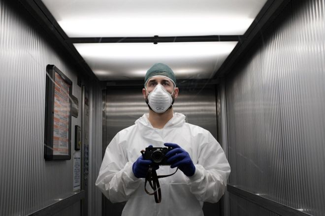 Nurse Paolo Miranda holding a camera