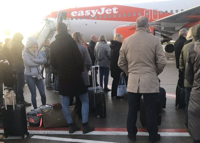 Passengers wait to board a flight in Liverpool after being forced to disembark