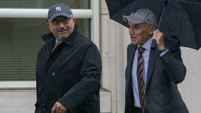 Abogados de El Chapo caminando hacia la corte bajo una sombrilla.