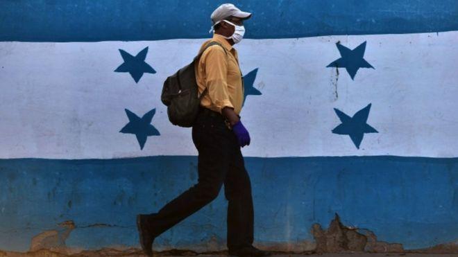 Hondureño con mascarilla ante la bandera nacional.
