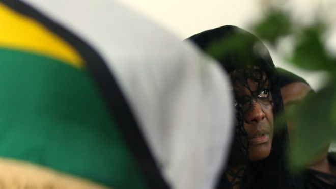 """Grace Mugabe widow of former Zimbabwean President Robert Mugabe sits beside her husband""""s coffin at their """"Blue Roof"""" residence in Harare, Zimbabwe, September 12, 2019."""