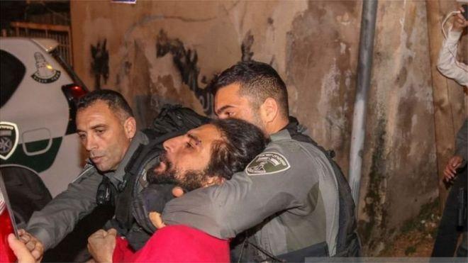 شاب في قبضة عناصر ترتدي زي الشرطة الإسرائيلية
