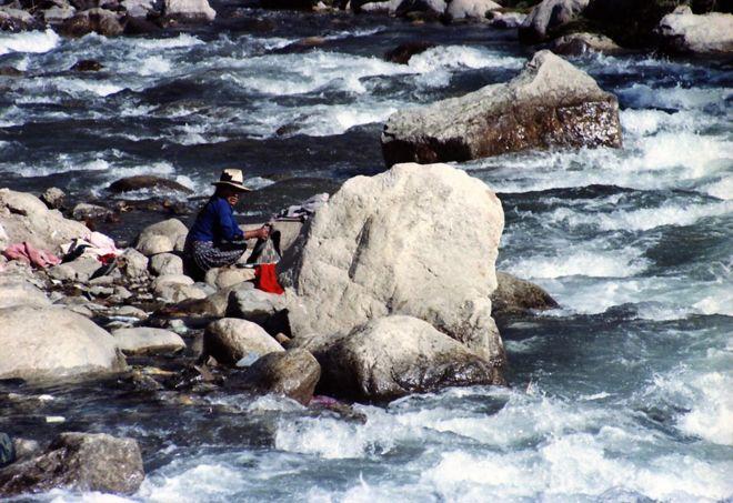 أمرأة تغسل الثياب في مياه متدفقة