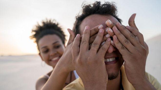 Hombre y mujer tapándole los ojos en una playa