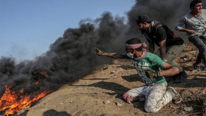 Un palestino apunta con su tirachinas a los soldados israelíes en la frontera de Gaza.