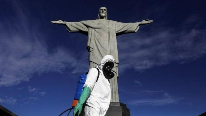 Seorang pekerja yang mengenakan pakaian pelindung berdiri di depan patung Kristus Sang Penebus di Brasil
