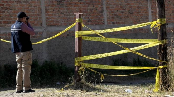 A forensic expert takes a photo at the site where a mass grave was discovered at El Mirador neighbourhood in Tlajomulco de Zuniga