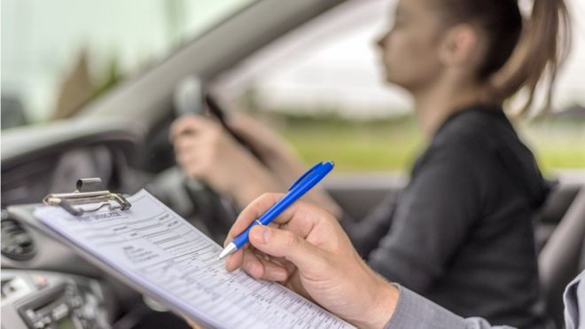 Young woman in car taking driving test