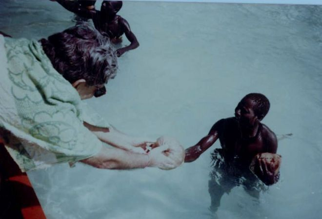 TN Pandit regalando un coco a un hombre sentinelés.