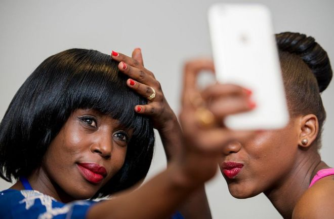 Two women pose for a selfie before Swahili Fashion Week in Dar es Salaam, Tanzania on 4 December 2015.
