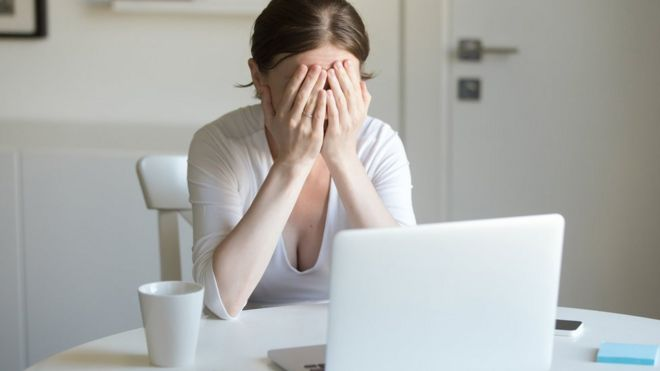 Woman with her face in her hands in front of laptop