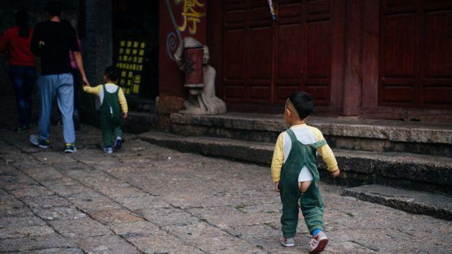 Crianças na rua usando calça aberta
