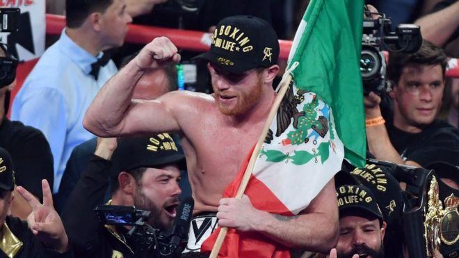 """Canelo"" Álvarez celebra su victoria sobre Golovkin con la bandera de México."