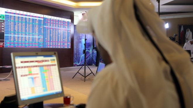 File photo showing a Qatari trader following the stock market at the Qatari stock exchange in Doha (31 July 2017)