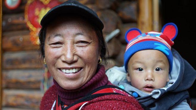 Mujer mosu con bebé a la espalda.