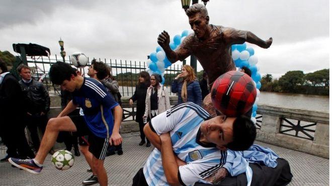 Мальчики играют с футбольными мячами перед статуей игрока Аргентины Лионеля Месси после ее открытия в Буэнос-Айресе, Аргентина, 28 июня 2016 года