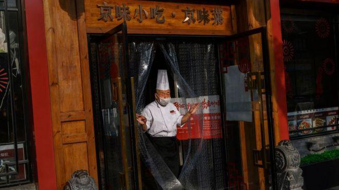 Un cocinero en la puerta de un restaurante con mascarilla en Pekín, el 2 de mayo.