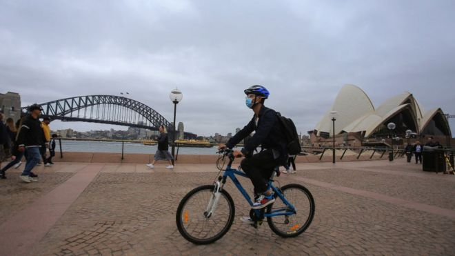 A man wears a face mask as a preventative measure against Coronavirus as he rides a bicycle past the Sydney Harbour Bridge and the Sydney Opera House.
