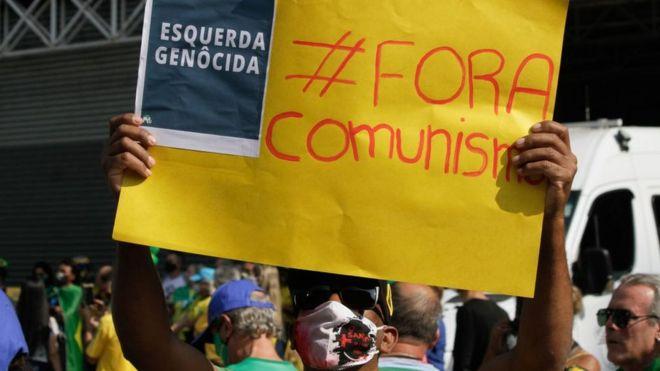 """Manifestante em SP com cartaz em que se lê: """"fora comunismo"""" e """"esquerda genocida"""""""