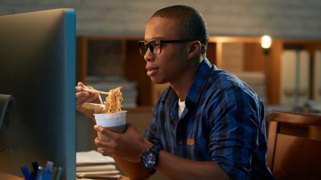 Homem comendo em frente ao computador
