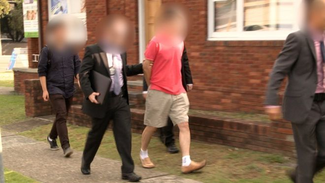A man with a blurred face is led away by police officers following his arrest