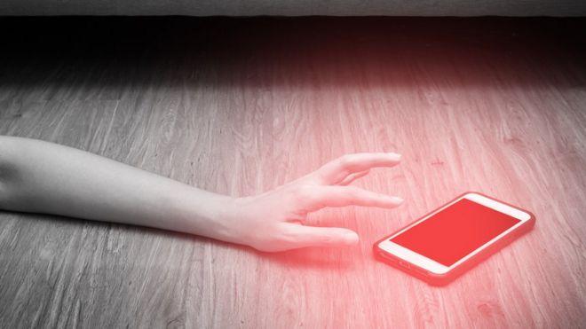 Imagem mostra braço se aproximando de celular