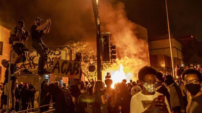 Protesto contra racismo nos Estados Unidos, com uma área pegando fogo e pessoas com cartazes