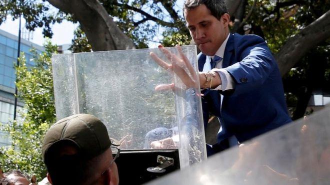 Juan Guaidó, trepado a una reja frente a la Asamblea Nacional.
