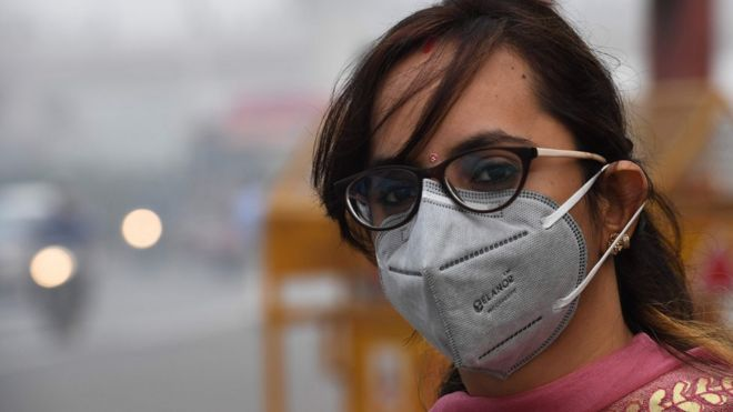 A woman wearing a protective face mask waits for public bus in smoggy conditions in New Delhi on November 4, 2019.