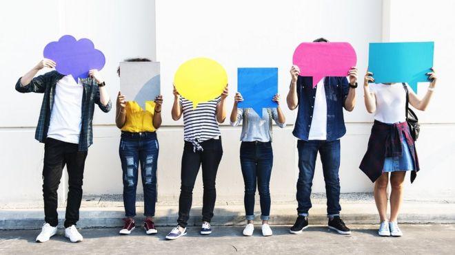 Seis pessoas seguram imagens coloridas de balões de diálogo