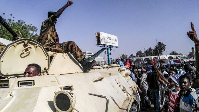Sudanese protesters salute a military armoured vehicle as they gather during a demonstration in front of the military headquarters in the capital Khartoum, 9 April 2019