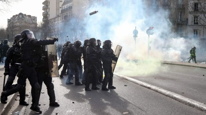 """Police officers throw tear gas to protesters during the 13th consecutive Saturday demonstration called by the """"Yellow Vests"""""""